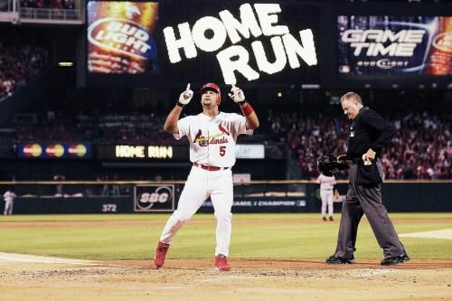 Albert Pujols points up to the sky as he crosses home plate