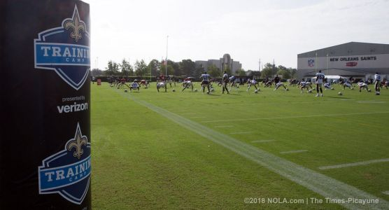 Two Saints players race motorized tackling dummy at practice