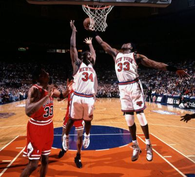Patrick Ewing grabs a rebound over New York Knicks teammate
