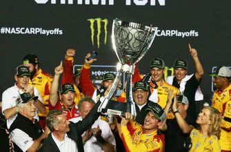 Steve Phelps presents Joey Logano with the Cup Series championship trophy